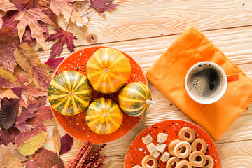 cup of coffee, decorative pumpkins, bagels and cane sugar on wooden table decorated by falling leaves, top view