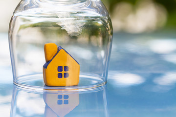 The concept of insurance and protection of housing. Miniature yellow toy house under a glass cap. Selective focus
