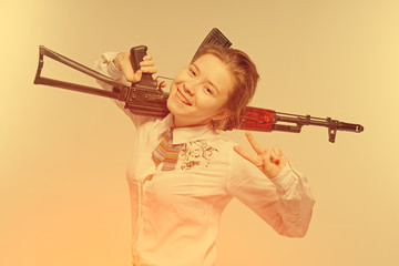 Girl smiling with Kalashnikov in hand. Isolated