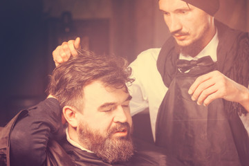 Man hairdresser doing hairstyle a man with a beard