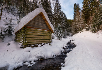 wooden building near the stream in snowy forest. lovely winter scenery, great place for hiking in fine weather