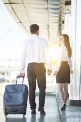 The business man and woman walk with a suitcase near modern building
