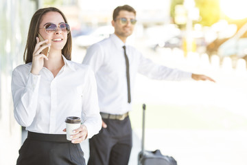 The smile woman hold a cup of coffee and phone on the background of the man