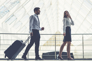 The happy business man and woman walk with a suitcase