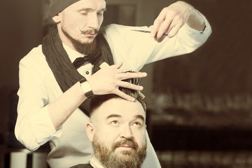 Stylist in black hat, bow tie and scarf makes hair a man with a beard