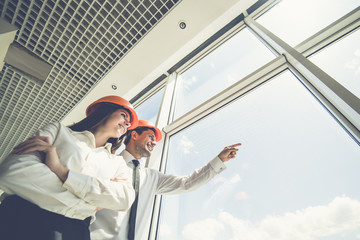The two engineers stand near the window and gesture