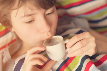 Cute teenager girl lying in bed and drinking coffee from a white cup. Toned