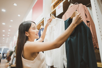Young Asian Woman with Shoulder Bag Looking at Clothes Hanging on the Rail Inside the Clothing Shop.