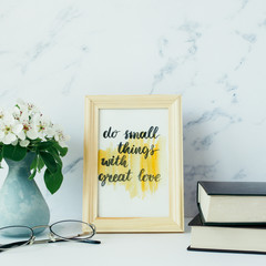 "Flowers of apple tree in vase, books, eyeglasses, card with inspiration quote ""do small things with great love"" in a wooden photo frame. Styled minimalistic still life"