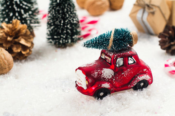 Miniature red car carrying fir tree on Christmas background. Selective focus