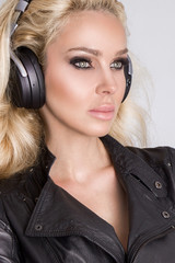 Beautiful sexy blonde woman with long hair and perfect body in black leather jacket with headphones on and listen to music and sensual looks