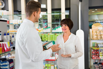 Man pharmacist helping customers in drug store