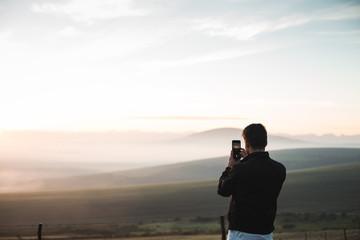 Man taking photos of nature on phone