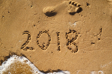 New Year is coming concept - 2018 written on a beach sand with wave of the sea