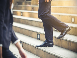 Close up legs of businessman and businesswoman in suit, walking down from stairs, go on business, go down, loss, retired, unemployment and quit from job concept