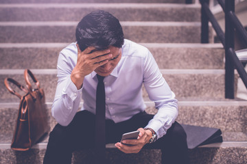 stressed businessman use smart phone sitting at stairway. worry about business situation