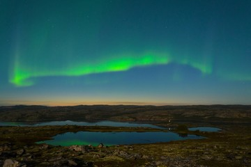 Autumn Aurora over the hills and reflected in the lake.