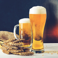 Fresh beer in two glasses against dark background. Concept of Octoberfest, food and drinking, toned image