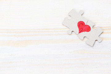 Heart made of two pieces of jigsaw puzzle on light wooden table, copyspace for text