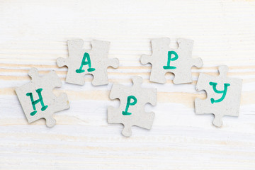 Word Happy made of four pieces of jigsaw puzzle on light wooden table, close-up