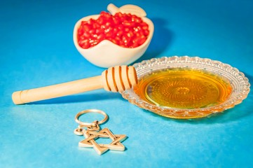 "Jewish symbols, the Jewish New Year Rosh Hashanah concept - apple shaped plate with red pomegranate seeds on a blue background with honey and Jewish David Star ""Magen David"". Rosh Hashanah greeting."