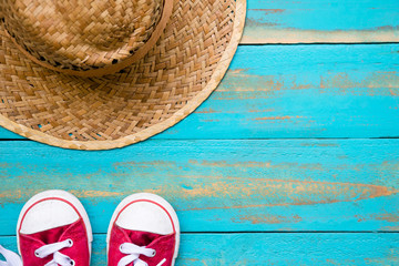the red sneakers with weave hat on old blue wooden floor background. copy space for graphic designer