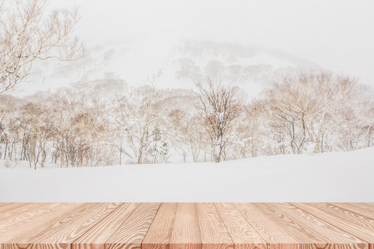 Wood shelf table with blurred background of mountain and trees in the snow.