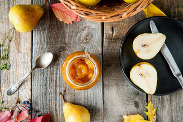 Top view Pear jam and fresh yellow ripe pears on old rustic wooden table. Autumn harvest still life concept. Selective focus. Flat lay
