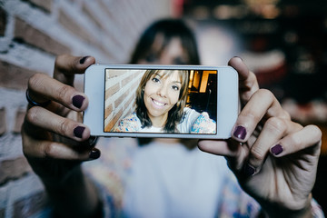 Young beautiful woman taking herself a portrait with her cellphone. Lifestyle photography