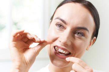 Young Woman Flossing Teeth In Bathroom