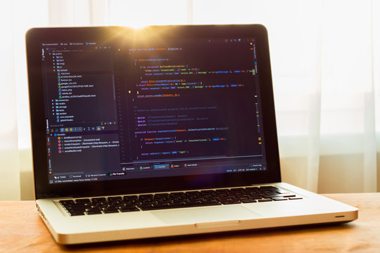 Php code on laptop (web developing) in sunlight