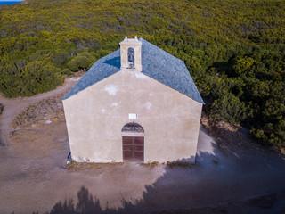 Vista aerea della cappella di Santa Maria, macchia Mediterranea, colline a ridosso della costa. Penisola di Cap Corse, Corsica. Tratto di costa. Francia