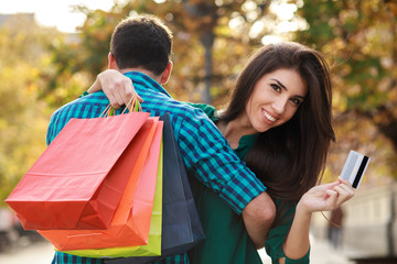 Young man hugging his girlfriend after shopping