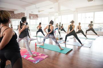 Group women stretching and practices yoga in a class, healthy lifestyle and fitness concept