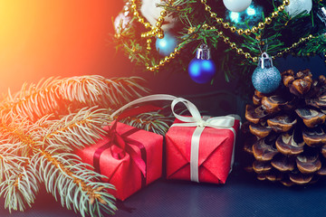 Pine cone and gifts wrapped in a red paper with white ribbon under decorated Christmas tree in rays of the sun. Concept of Merry Christmas and New Year, toned image
