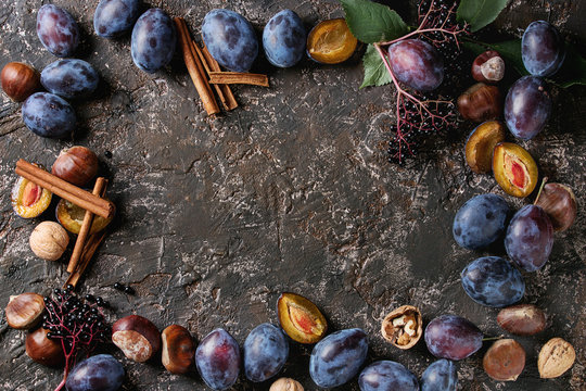 Autumn frame from plums, nuts, cinnamon over brown concrete background. Top view with space for text. Fall harvest and jam making concept.