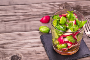 Glass of cucamelon and radish salad on wooden table with copy space