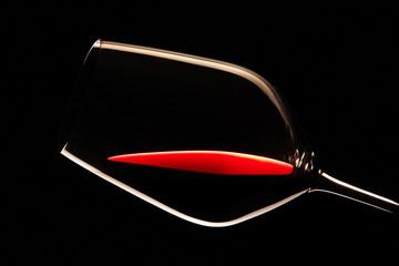 Glas mit Rotwein vor schwarzem Hintergrund