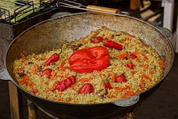 Плов из риса  кусков мяса и овощей в большом чане на кухне