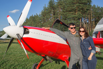 Young couple standing near airplane
