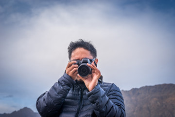 Tourist asian man in blue jacket coat taking photography with camera at Beautiful cloud blue sky