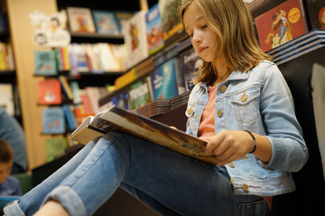 Young girl in book store reading comics