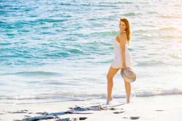 Young woman walking along the beach