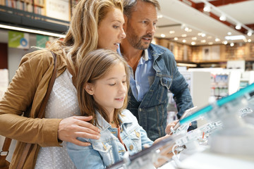 Family at the multimedia store looking at digital tablets