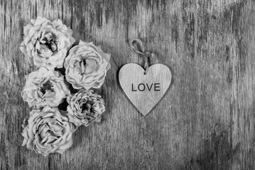 Dry withered roses and a heart on an old wooden background. Monochrome