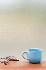 blue cup and eyeglass on the table