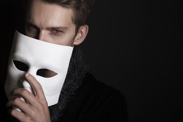 Mysterious man holding white mask