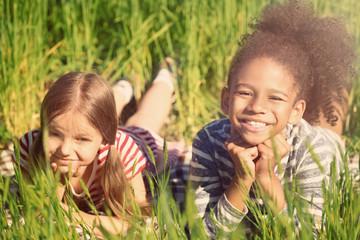 Happy little girls in green field Fototapete