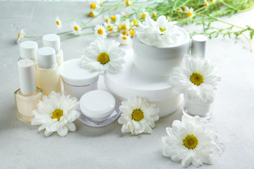 Composition with skin care products and chamomile flowers on table