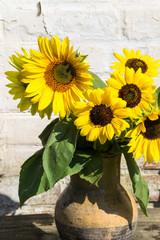 Sunflowers in vintage clay jug on wooden table